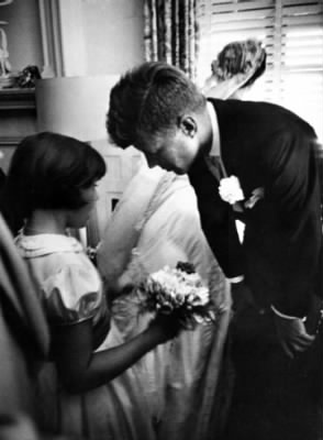 Janet Auchincloss, half sister of bride, talks to Kennedy while bride looks out window.jpg